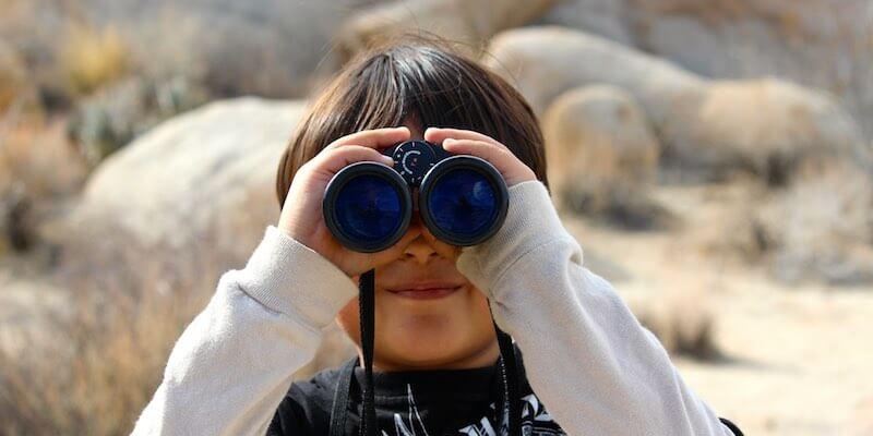 Kind mit Fernglas beim Beobachten